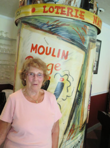 Pierrette Baldwin, who turns 80 in September, next to the vintage, atmospheric Chez Pierre decor created by Glens Falls artist Tom Mahoney.