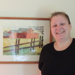 Megan Clothier in her Lake George home, with a watercolor she painted since suffering a traumatic brain injury. She now advocates for TBI survivors as a member of the New York State Brain Injury Coordinating Council.