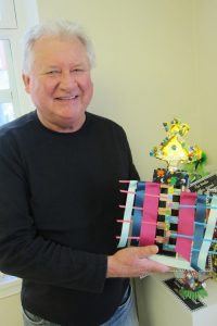 """John Strong, director of the Lake George Arts Project, with hand-""""enhanced"""" trophies to be awarded at this Saturday's Black Velvet Art Party. Chronicle photos/Cathy DeDe"""