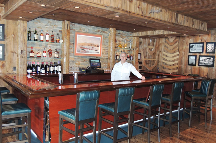 Algonquin Restaurant owner Keith Scott in the new Topside Hacker-Craft mahogany bar, complete with custom-stitched Hacker cushions on the bar stools. Chronicle photos/Gordon Woodworth