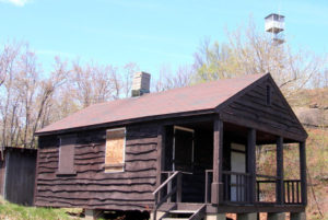 A preserved fire tower, seen in background of cabin photo, stands atop Hadley Mountain.