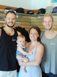 "Sara Pfau holding her daughter, Mira. Sara's brother Domenick, left, and Matt Peterson co-own the store ""Local"" in Bolton Landing that fuels the craze."