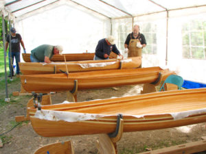 Instructor Larry Benjamin, right, at the Adirondack Folk School in Lake Luzerne, watches as students Matt Moore (center) and his brother Ed put the finishing touches on a handmade cedar strip canoe. Chronicle photo/David Cederstrom